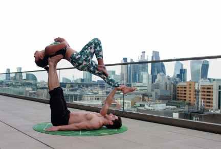 man lying down on mat while lifting woman